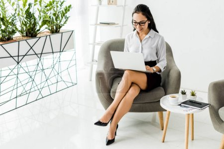 Photo for Beautiful smiling asian businesswoman in glasses sitting on armchair and using laptop in office - Royalty Free Image