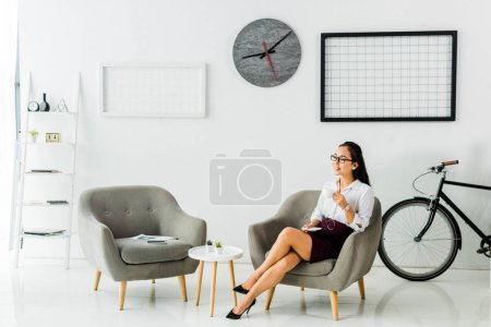 Photo pour Sourire de femme d'affaires asiatique assis sur le fauteuil avec une tasse de café dans le bureau moderne - image libre de droit