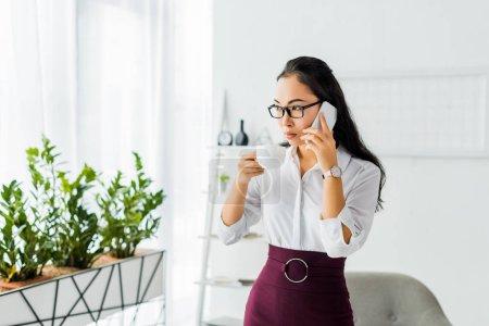 Photo pour Belle grave asiatique femme d'affaires parler sur smartphone tout en ayant pause café dans le bureau - image libre de droit