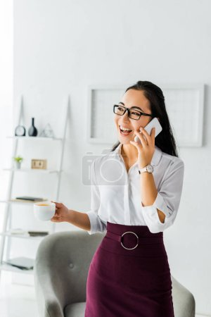 Photo for Beautiful laughing asian businesswoman talking on smartphone while having coffee break in office - Royalty Free Image
