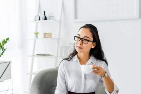 Photo for Selective focus of beautiful asian businesswoman in glasses having coffee break in office - Royalty Free Image