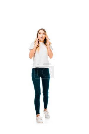 full length view of scared young woman looking at camera isolated on white