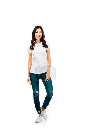 vista completa de la hermosa chica morena en camiseta blanca y jeans sonriendo a la cámara aislada en blanco