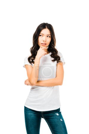 thoughtful young woman standing with hand on chin and looking away isolated on white