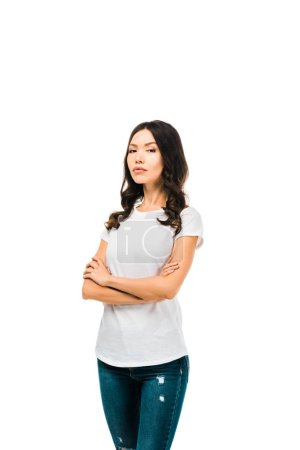 confident young woman standing with crossed arms and looking at camera isolated on white