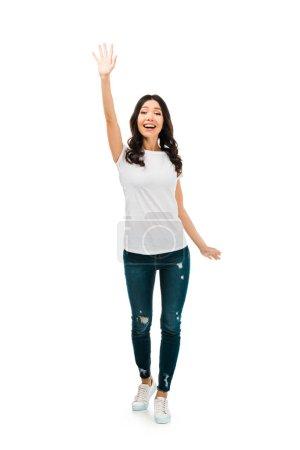 full length view of happy brunette girl waving hand isolated on white