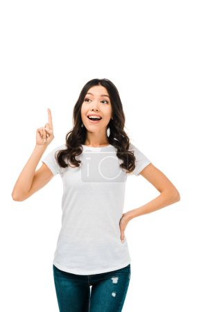 smiling young woman pointing up with finger and looking away isolated on white