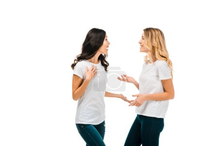 happy young women in white t-shirts talking and looking at each other isolated on white