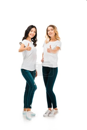 full length view of happy young women showing thumbs up and smiling at camera isolated on white