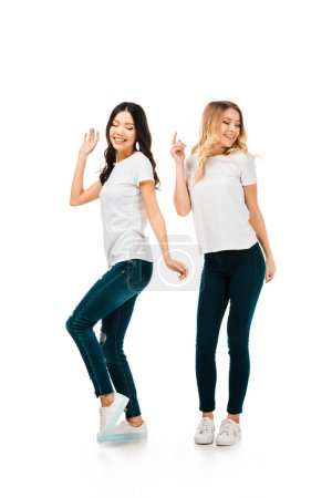 full length view of beautiful happy girls in white t-shirts dancing isolated on white