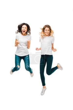 excited young women jumping and smiling at camera isolated on white