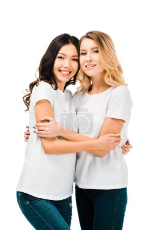 happy young women in white t-shirts hugging and smiling at camera isolated on white