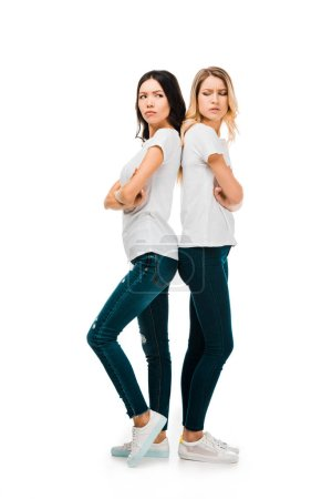 full length view of upset young women standing back to back with crossed arms isolated on white