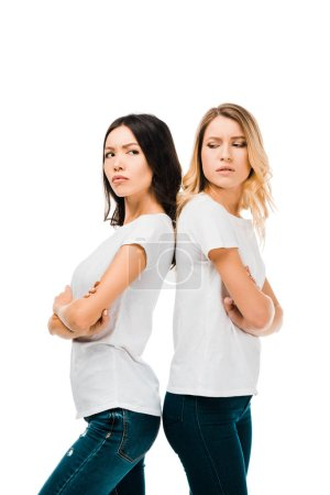 side view of upset young women standing back to back with crossed arms isolated on white