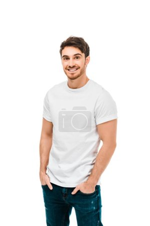 handsome happy young man standing with hands in pockets and smiling at camera isolated on white