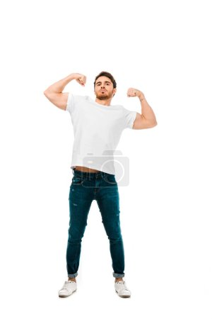 confident young man showing biceps and looking at camera isolated on white