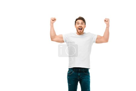 excited young man showing muscles and smiling at camera isolated on white