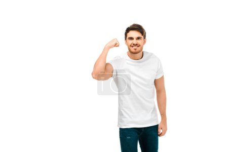 handsome young man showing biceps and smiling at camera isolated on white