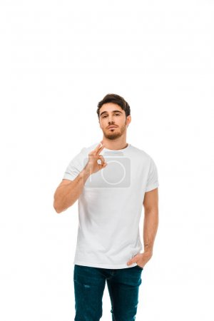 confident young man showing ok sign and looking at camera isolated on white