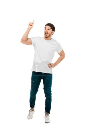 full length view of young man standing with hand on waist and pointing up with finger isolated on white
