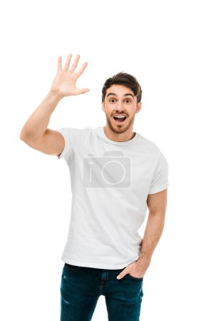 cheerful young man waving hand and smiling at camera isolated on white