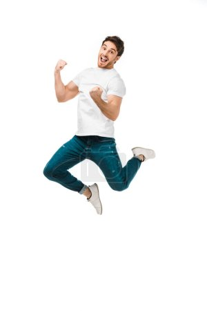 excited young man jumping and smiling at camera isolated on white