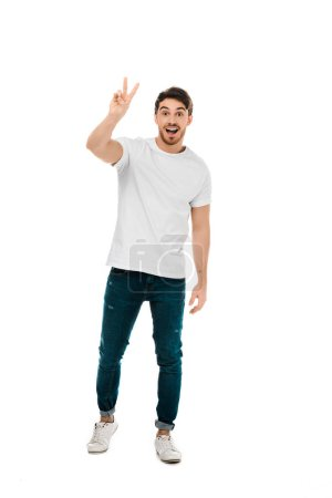full length view of happy young man showing victory sign and smiling at camera isolated on white
