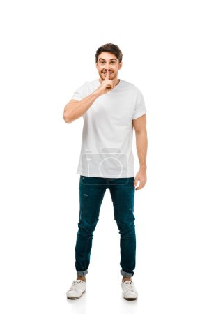 full length view of man in white t-shirt gesturing for silence with finger on lips and looking at camera isolated on white