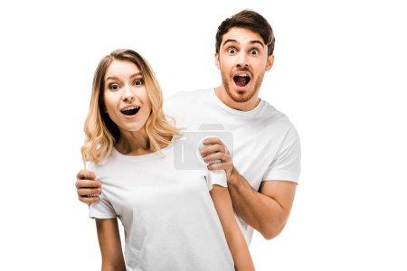 Photo pour Surpris jeune couple en t-shirts blancs regardant caméra isolé sur blanc - image libre de droit