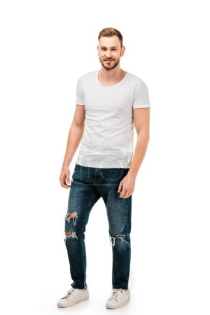 Photo for Full length view of handsome young man in white t-shirt and jeans smiling at camera isolated on white - Royalty Free Image