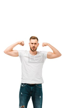 handsome bearded young man showing biceps and looking at camera isolated on white