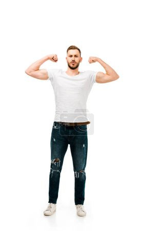 full length view of handsome bearded young man showing biceps and looking at camera isolated on white