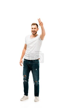 full length view of handsome happy man showing victory sign and looking at camera isolated on white