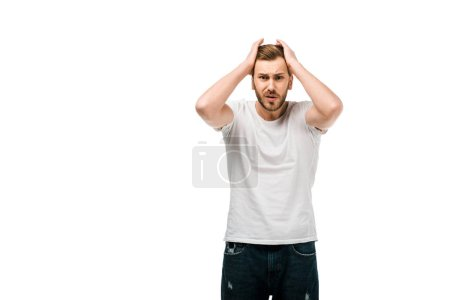 frustrated young man in white t-shirt standing with hands on head and looking at camera isolated on white