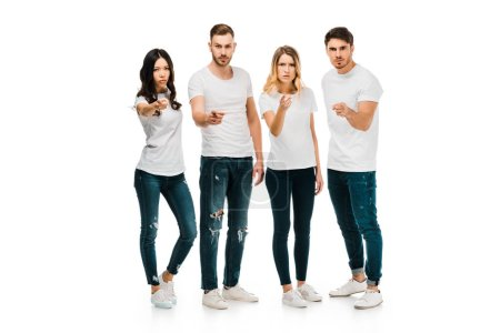 serious young people standing together and pointing at camera isolated on white