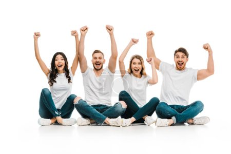 excited young friends in white t-shirts sitting and raising hands isolated on white