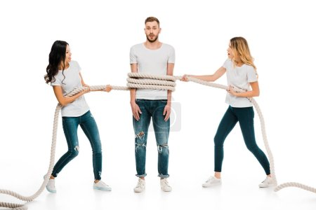young women holding rope around scared young man isolated on white