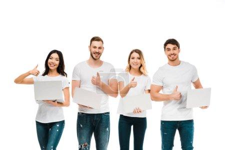 Foto de Feliz jóvenes sosteniendo portátiles y mostrando pulgar hacia arriba aislado en blanco - Imagen libre de derechos