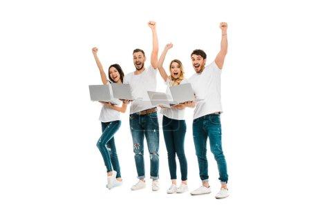 Photo pour Excités jeunes amis avec des ordinateurs portables levant la main et souriant à la caméra isolée sur blanc - image libre de droit