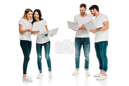smiling young men and women standing together and using laptops isolated on white
