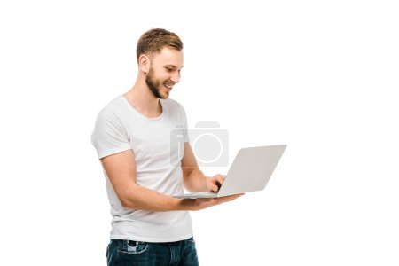 handsome smiling young man in white t-shirt using laptop isolated on white