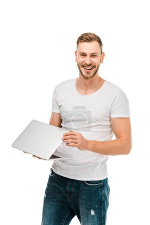 handsome young man holding laptop and smiling at camera isolated on white
