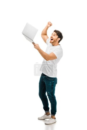 excited young man holding laptop and shaking fist isolated on white