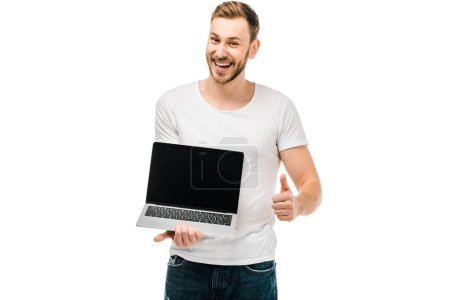 happy young man holding laptop with blank screen and showing thumb up isolated on white