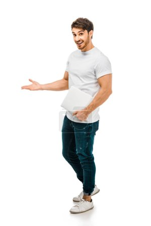 full length view of handsome young man holding laptop and smiling at camera isolated on white