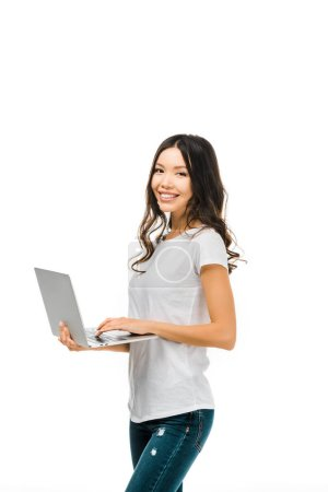 happy young woman using laptop and smiling at camera isolated on white