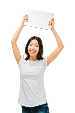 happy young woman holding laptop above head and smiling at camera isolated on white