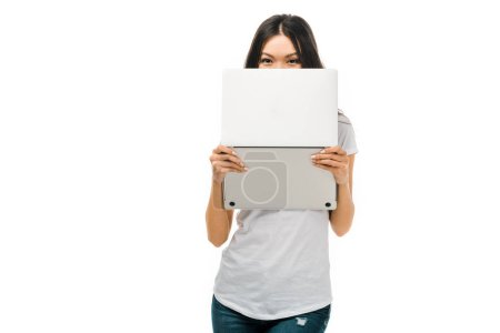 young brunette woman holding laptop and looking at camera isolated on white