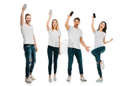 full length view of happy young men and women holding smartphones and smiling at camera isolated on white