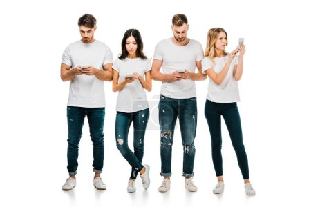 Photo for Full length view of young friends in white t-shirts and jeans using smartphones isolated on white - Royalty Free Image